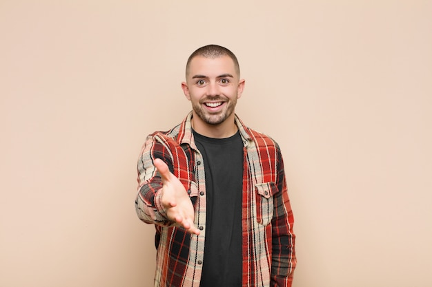Jeune bel homme souriant, heureux, confiant et sympathique, offrant une poignée de main pour conclure un accord, coopérant sur le mur