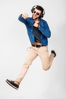 Jeune bel homme souriant heureux dansant et écoutant de la musique dans des écouteurs isolé sur fond de studio blanc, portant chemise en jean et lunettes de soleil, gagnant sautant dans le succès