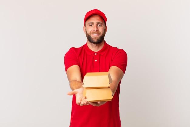Jeune bel homme souriant joyeusement avec amical et offrant et montrant un concept de livraison de hamburger