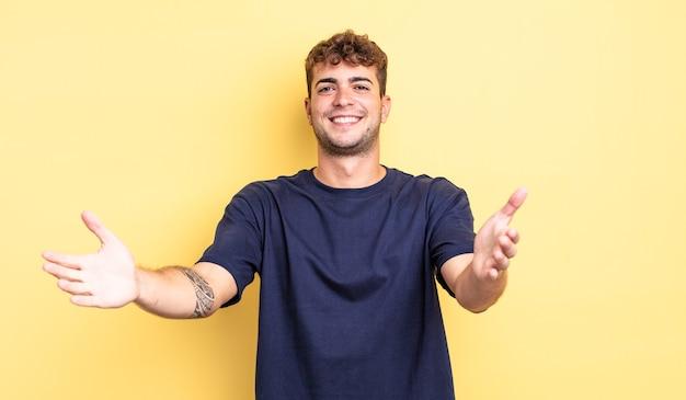 Jeune bel homme souriant joyeusement donnant un câlin de bienvenue chaleureux, amical et affectueux, se sentant heureux et adorable