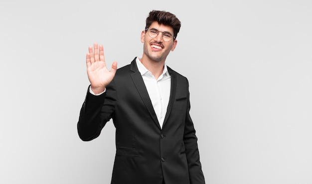 Jeune bel homme souriant joyeusement et gaiement, en agitant la main, en vous accueillant et en vous saluant, ou en vous disant au revoir