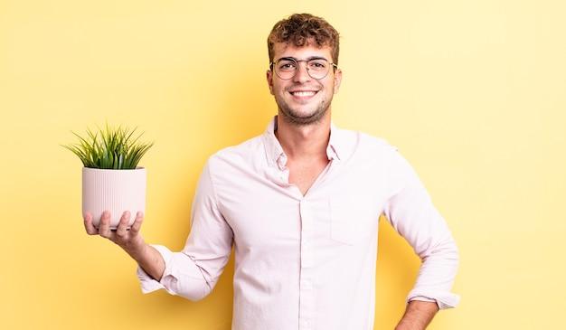Jeune bel homme souriant joyeusement avec une main sur la hanche et confiant. concept de plante décorative