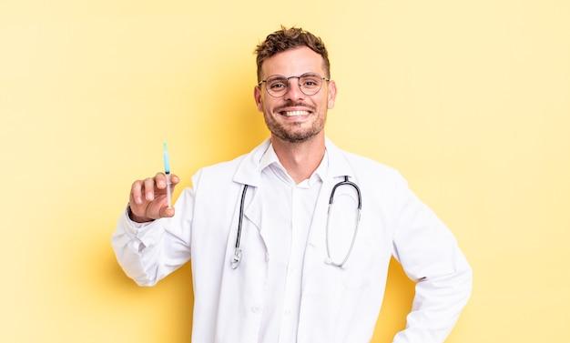 Jeune bel homme souriant joyeusement avec une main sur la hanche et confiant. concept de seringue de médecin