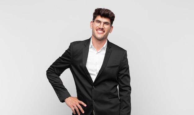 Jeune bel homme souriant joyeusement avec une main sur la hanche et confiant
