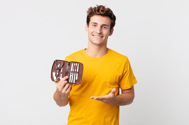 Jeune bel homme souriant joyeusement, se sentant heureux et montrant un concept et tenant un étui à outils à ongles