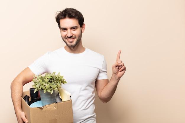 Jeune bel homme souriant joyeusement, se sentant heureux et pointant vers le côté et vers le haut, montrant l'objet dans l'espace de copie
