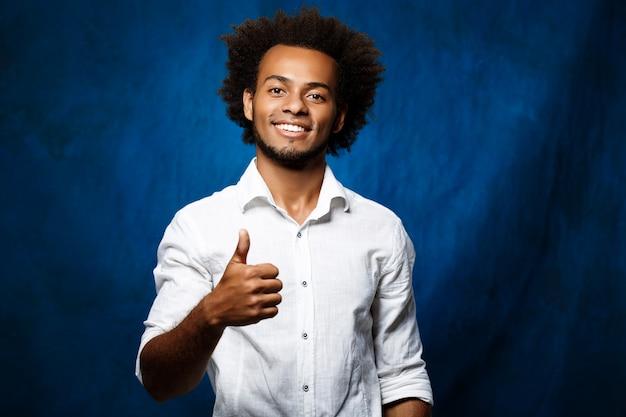 Jeune bel homme souriant, montrant bien sur la surface bleue