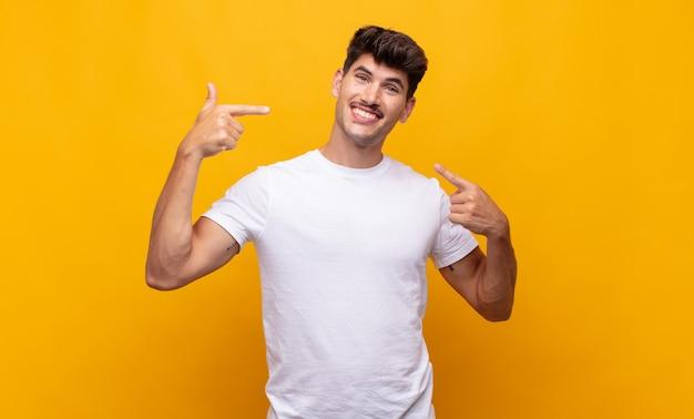 Jeune bel homme souriant pointant avec confiance vers son propre large sourire, attitude positive, détendue et satisfaite