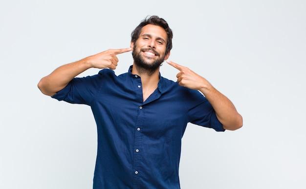 Jeune bel homme souriant pointant avec confiance vers son propre large sourire