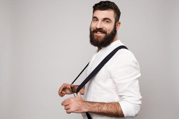 Jeune bel homme souriant posant sur blanc.