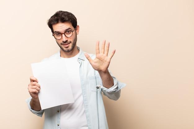 Jeune bel homme souriant et à la recherche amicale, montrant le numéro cinq ou cinquième avec la main en avant, compte à rebours