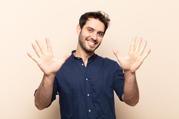 Jeune bel homme souriant et à la recherche amicale, montrant le numéro dix ou dixième avec la main en avant, compte à rebours