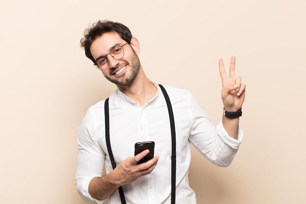 Jeune bel homme souriant et à la recherche de bonheur, amical et satisfait, gesticulant la victoire ou la paix à deux mains