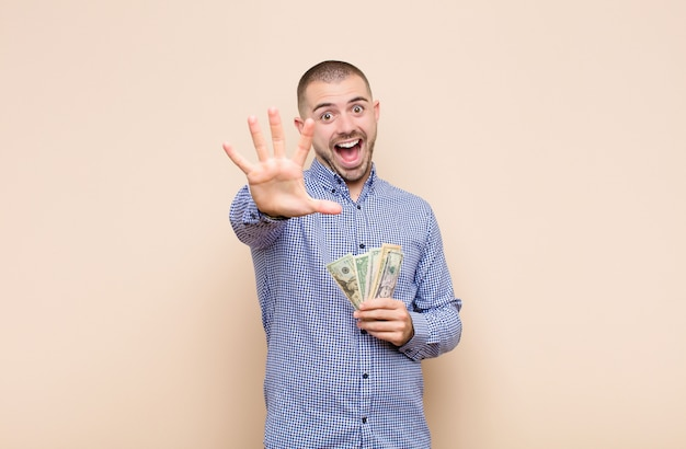 Jeune bel homme souriant et regardant amical, montrant le numéro cinq ou cinquième avec la main vers l'avant, compte à rebours avec des billets en dollars