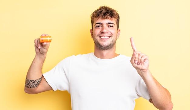 Jeune bel homme souriant et semblant amical, montrant le numéro un avec une batterie