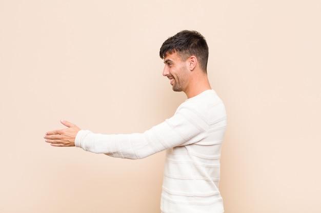 Jeune bel homme souriant, vous saluant et offrant une poignée de main pour conclure une affaire réussie, concept de coopération sur un mur chaud