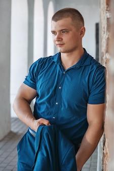 Jeune bel homme sportif dans un costume bleu sur fond de mur de briques en été.