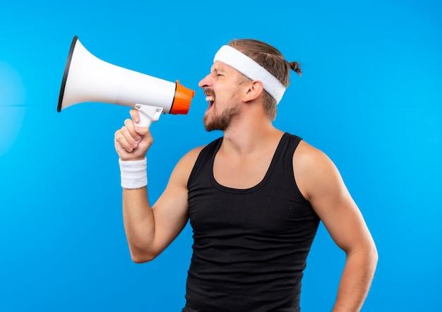 Jeune bel homme sportif portant bandeau et bracelets criant dans haut-parleur isolé sur l'espace bleu