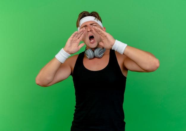 Jeune bel homme sportif portant un bandeau et des bracelets avec des écouteurs sur le cou mettant les mains près de la bouche appelant à quelqu'un isolé sur fond vert