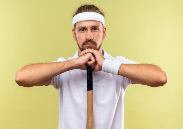 Jeune bel homme sportif portant bandeau et bracelets tenant une batte de baseball et mettant la tête sur les mains à la recherche d'isolement sur l'espace vert