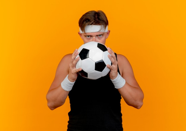 Jeune bel homme sportif portant bandeau et bracelets tenant et regardant par derrière un ballon de football à la caméra isolée sur fond orange