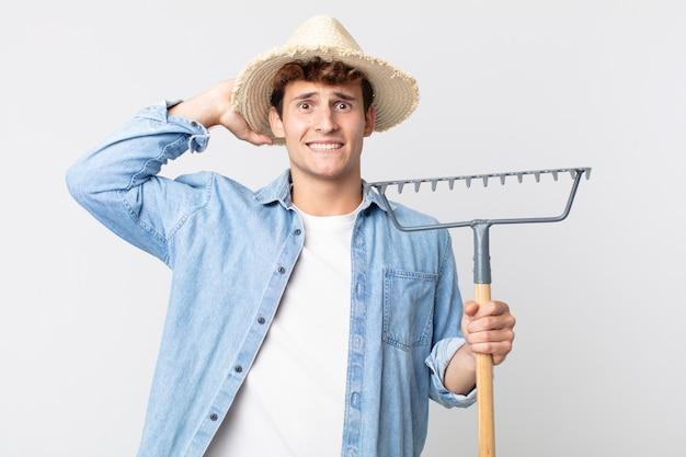 Jeune bel homme stressé, anxieux ou effrayé, les mains sur la tête. concept d'agriculteur
