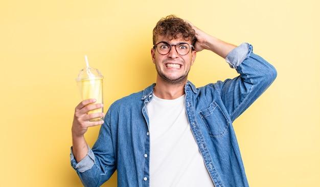 Jeune bel homme stressé, anxieux ou effrayé, les mains sur la tête. concept de milk-shake