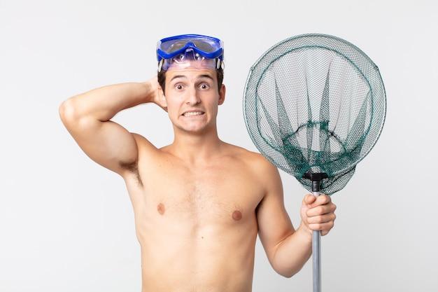 Jeune bel homme stressé, anxieux ou effrayé, les mains sur la tête avec des lunettes et un filet de pêche