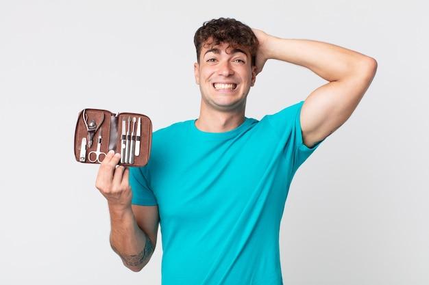 Jeune bel homme stressé, anxieux ou effrayé, les mains sur la tête et tenant un étui à outils pour les ongles