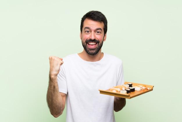 Jeune bel homme avec sushi sur mur végétal isolé célébrant une victoire en position de gagnant