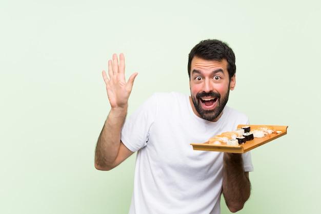 Jeune bel homme avec sushi sur mur végétal isolé nerveux et effrayé