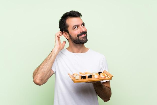 Jeune bel homme avec sushi sur mur végétal isolé, pensant à une idée