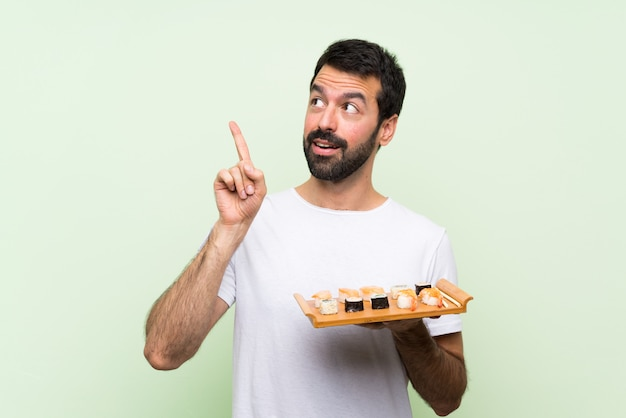 Jeune bel homme avec sushi sur mur vert isolé, pensant une idée pointant le doigt vers le haut