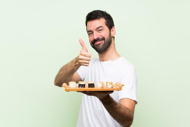 Jeune bel homme avec sushi sur mur vert isolé avec les pouces vers le haut parce que quelque chose de bien est arrivé