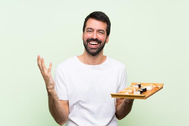 Jeune bel homme avec sushi sur mur vert isolé souriant beaucoup