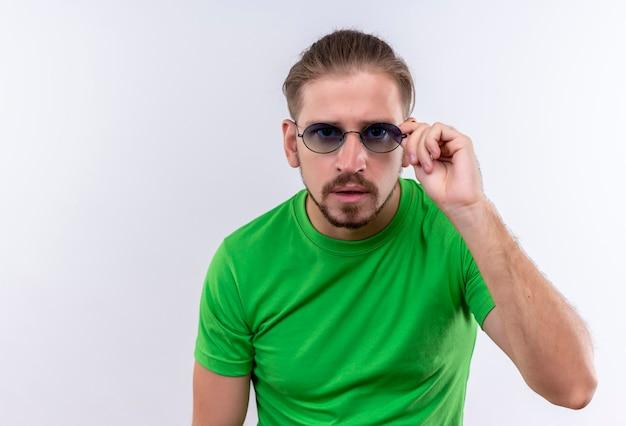 Jeune bel homme en t-shirt vert portant des lunettes à la caméra ar surpris debout sur fond blanc