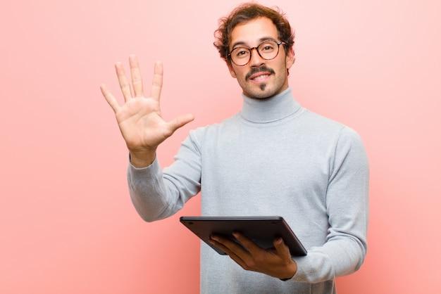 Jeune bel homme avec une tablette contre un mur plat rose
