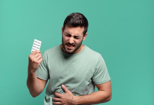 Jeune bel homme avec une tablette de pilules. concept de maladie ou de douleur