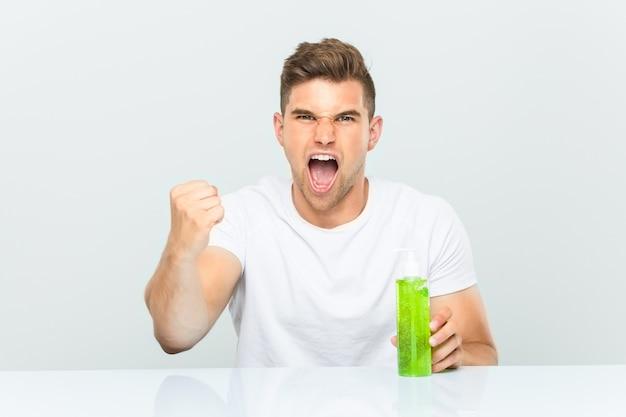 Jeune bel homme tenant une bouteille d'aloe vera acclamant insouciant et excité. concept de victoire.