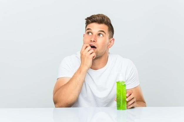 Jeune bel homme tenant une bouteille d'aloe vera détendu en pensant à quelque chose en regardant un espace de copie.