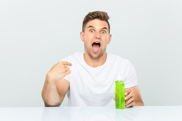 Jeune bel homme tenant une bouteille d'aloe vera surpris, se pointant lui-même, souriant largement.