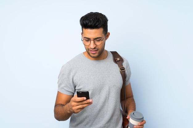 Jeune bel homme tenant un café à emporter et un téléphone portable
