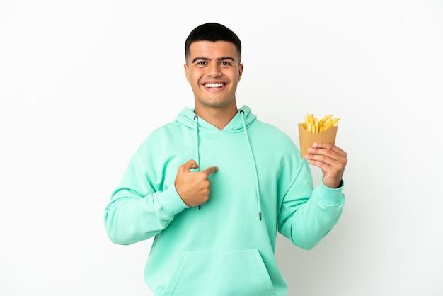 Jeune bel homme tenant des chips frites sur fond blanc isolé avec une expression faciale surprise