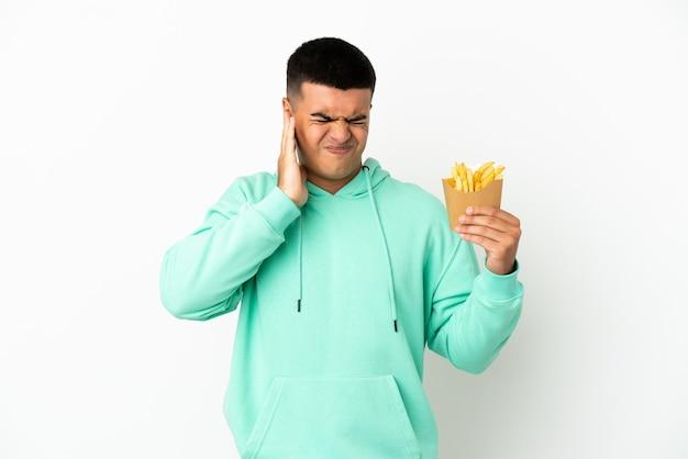 Jeune bel homme tenant des chips frites sur fond blanc isolé frustré et couvrant les oreilles