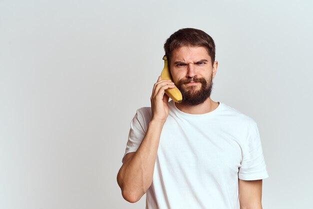 Jeune bel homme tenant des fruits isolés