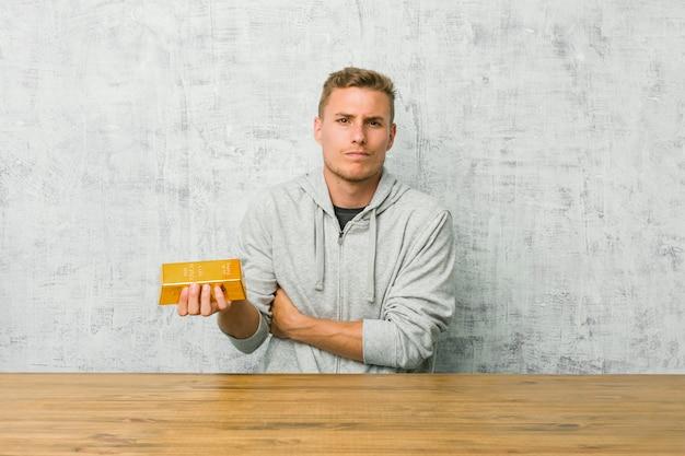 Jeune bel homme tenant un lingot d'or sur une table malheureuse à la recherche d'expression sarcastique.