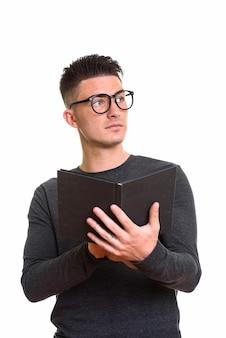 Jeune bel homme tenant un livre en pensant