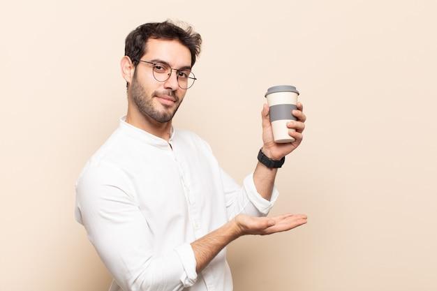 Jeune bel homme tenant un objet à deux mains sur le côté de l'espace de copie, montrant, offrant ou annonçant un objet