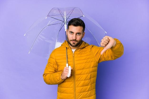 Jeune bel homme tenant un parapluie isolé montrant un geste de dégoût, pouces vers le bas