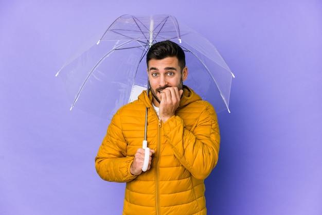 Jeune bel homme tenant un parapluie isolé des ongles mordants, nerveux et très anxieux.